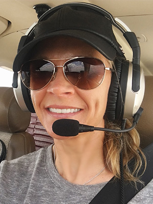 Cool Girl Natalie Kelley in plane with pilot's gear.