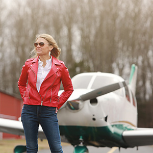 Cool Girl Natalie Kelley in front of small airplane.