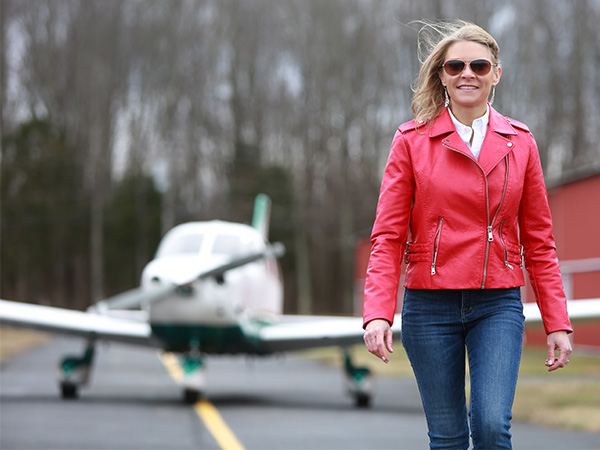 Cool Girl and pilot Natalie Kelley walking in front of a small airplane.